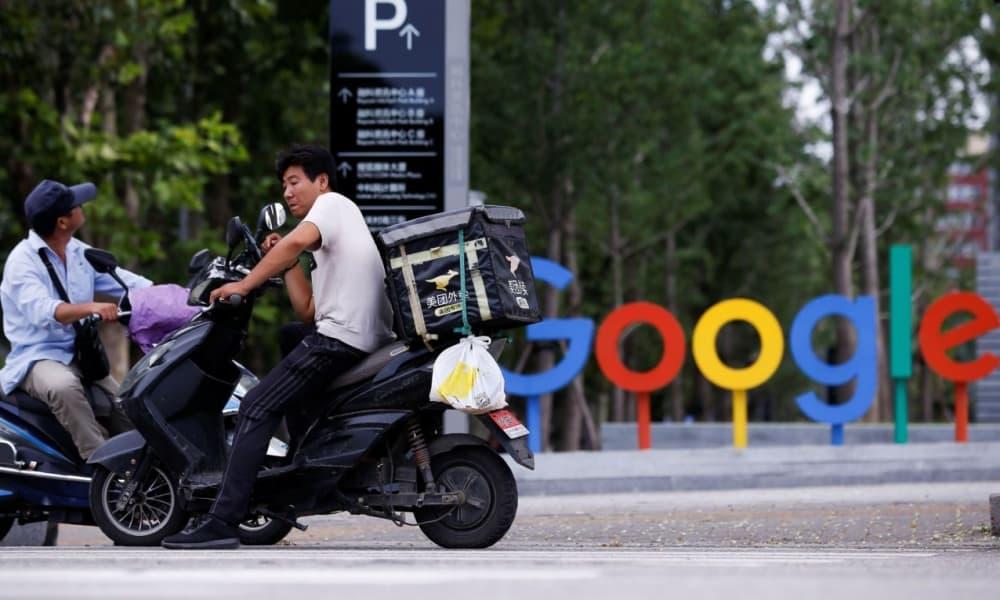 Repartidor en scooter parado cerca del logo de Google en Beijing, China