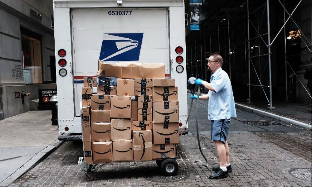 Trabajador del Servicio Postal de Estados Unidos entrega paquetes de Amazon.