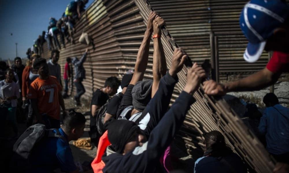 Migrantes saltan la barrera que divide México con EU en Tijuana.